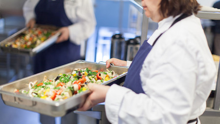 A woman in a white white coat with an apron carries a large pan filled with food| BERAS Implementation project goes global| Interreg Baltic Sea Region