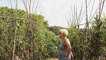 A blond woman in a dress standing in the midst of large potatoe plants| BERAS Implementation project goes global| Interreg Baltic Sea Region