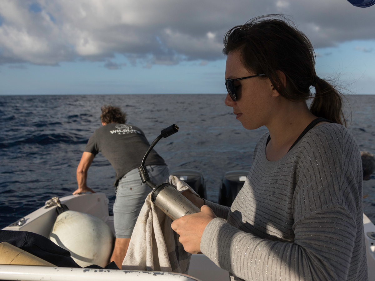 A young lady on a ship, holding a hydrophone.